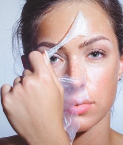 Close-up beauty portrait of a beautiful, natural young woman removing face mask. Copy space has been left